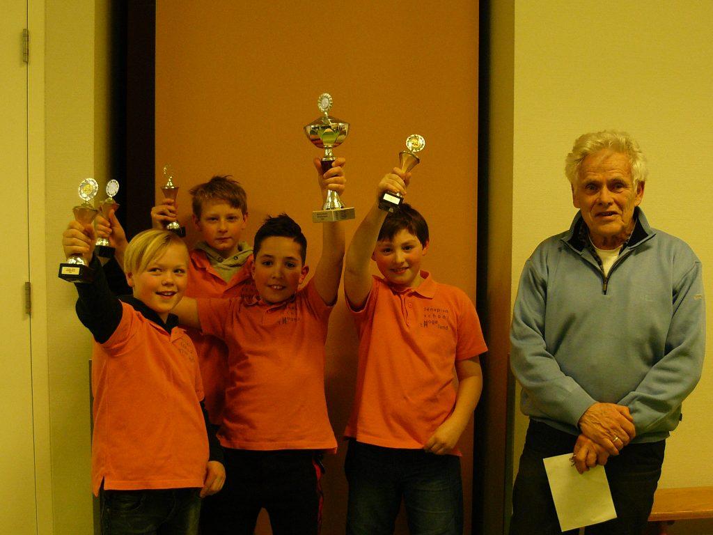 De spelers van jenaplanschool 't Hoge Land uit Epe heffen de bekers die ze uit handen van wedstrijdleider Helmig van der Vegt hebben ontvangen. (foto's Jan Flierman)