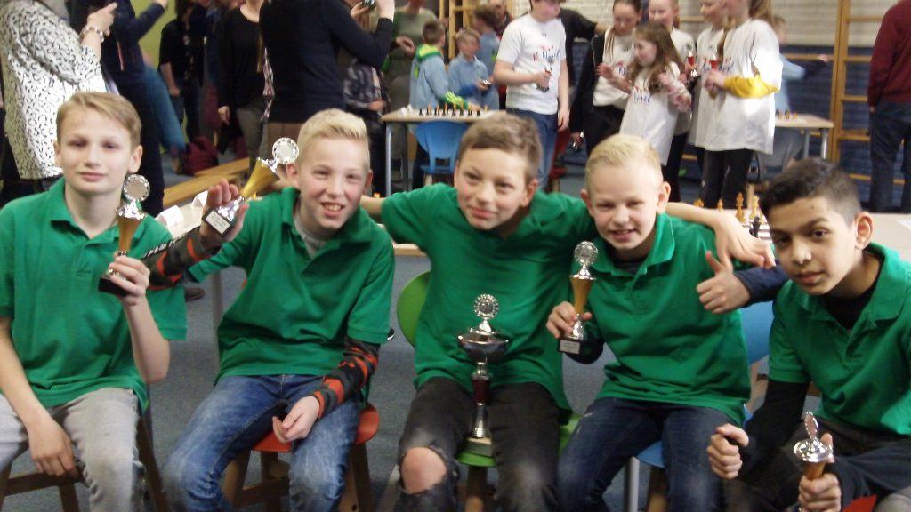De vijf winnende schakers van de Gildeschool heffen de wisselbeker en de individuele bekers. (foto's Andries Elskamp)